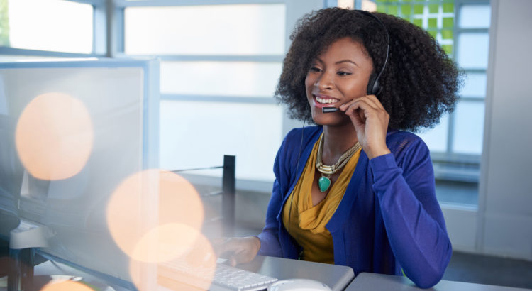 Friendly african american casual call center emplyee working at a desktop computer in a modern withe office