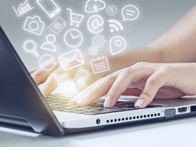 woman typing on laptop computer and media app icons flying. There is a warm glow on fingers.